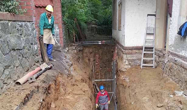 Baustelle Talhaus: ein tiefer Graben ist neben den Außenmauern offen, zwei Bauarbeiter sind zu erkennen