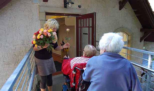 eine Mitarbeiterin begrüßt zwei Seniorinnen, eine sitzt im Rollstuhl