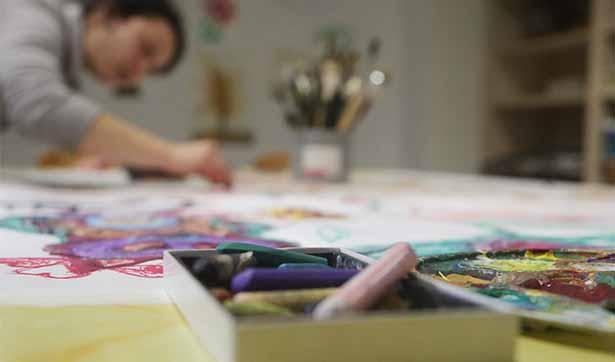 bunte Farben und Kreide stehen auf einem Tisch, im Hintergrund malt eine Frau