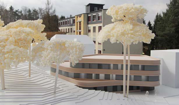 Modell mit beiger Fassade und abgerundeten Kanten, im Hintergrund Klinikgebäude
