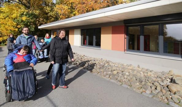eine Gruppe von Menschen, dabei ein Rollstuhlfahrer, stehen vor einem moderne Gebäude mit vielen Fenstern