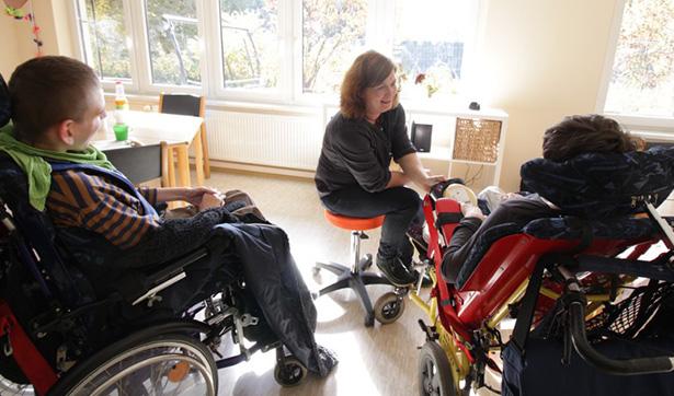 eine Betreuerin kümmert sich um zwei behinderte Menschen in speziellen Rollstühlen